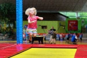 Little girl having fun at a trampoline park.