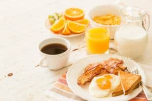 eggs over easy, bacon, toast, orange juice, milk, and coffee